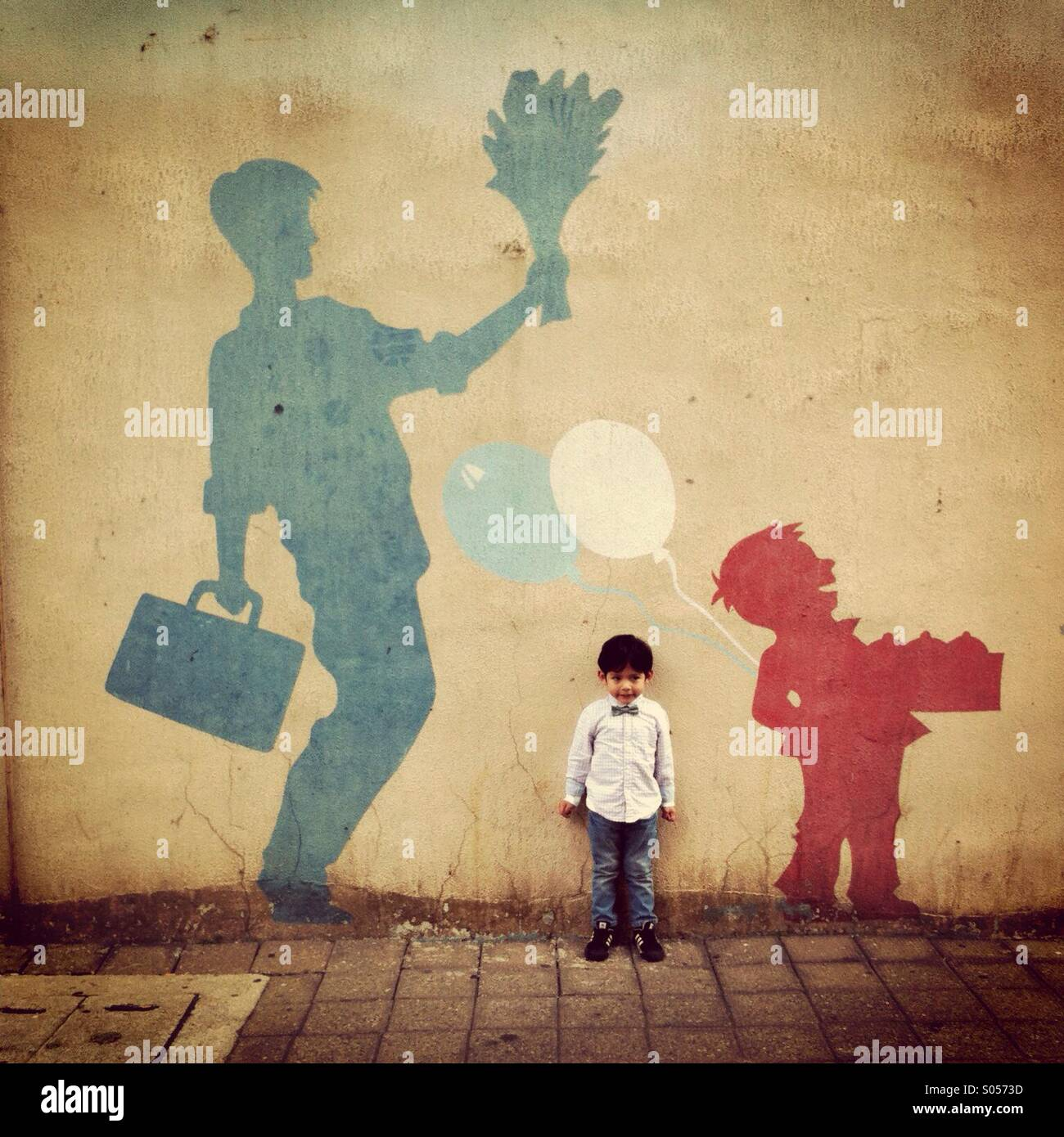 A little boy is posing in front of a paint on the wall Stock Photo ...
