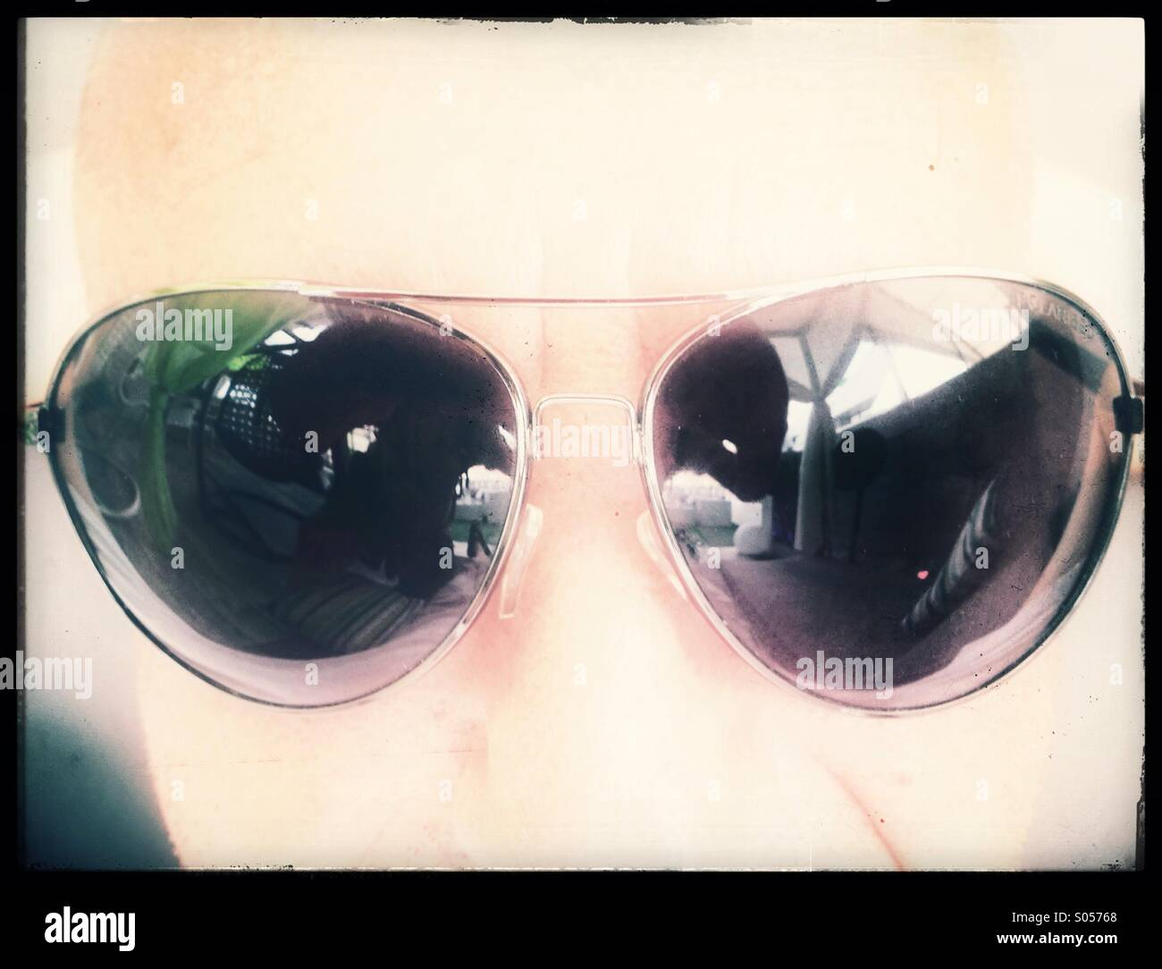 Man's face wearing dark glasses. - Stock Image