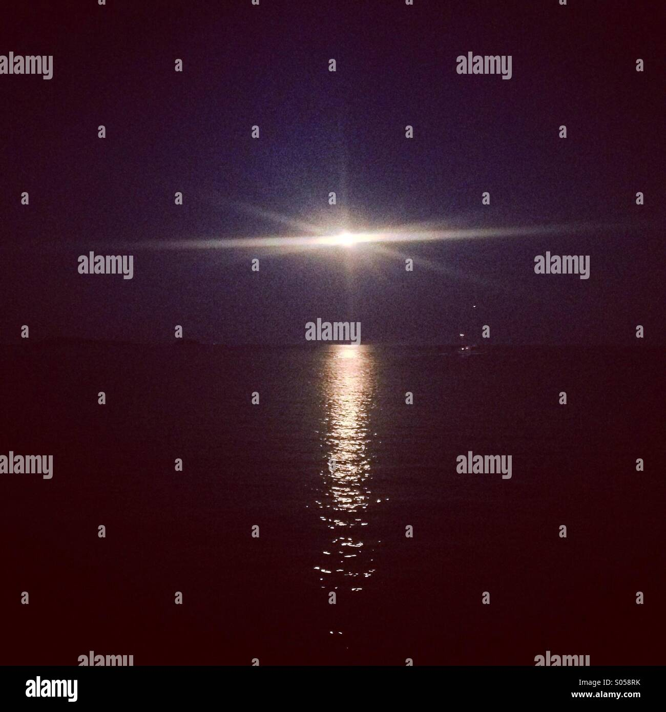 The moon at night time reflecting onto a dark sea - Stock Image