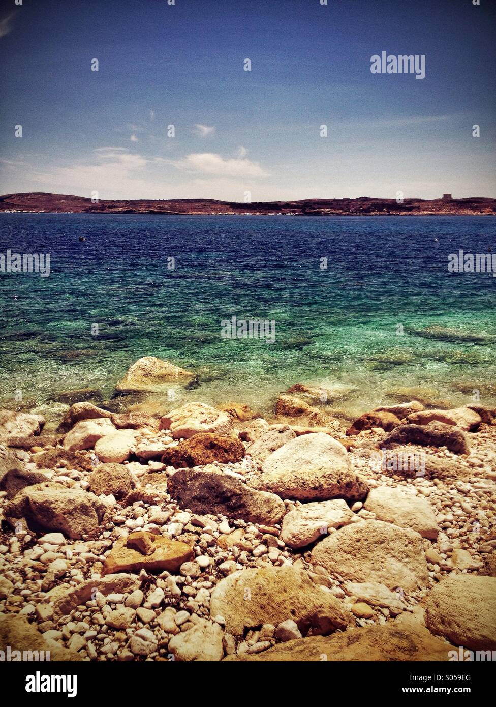 Rocky shore leading to blue sea - Stock Image