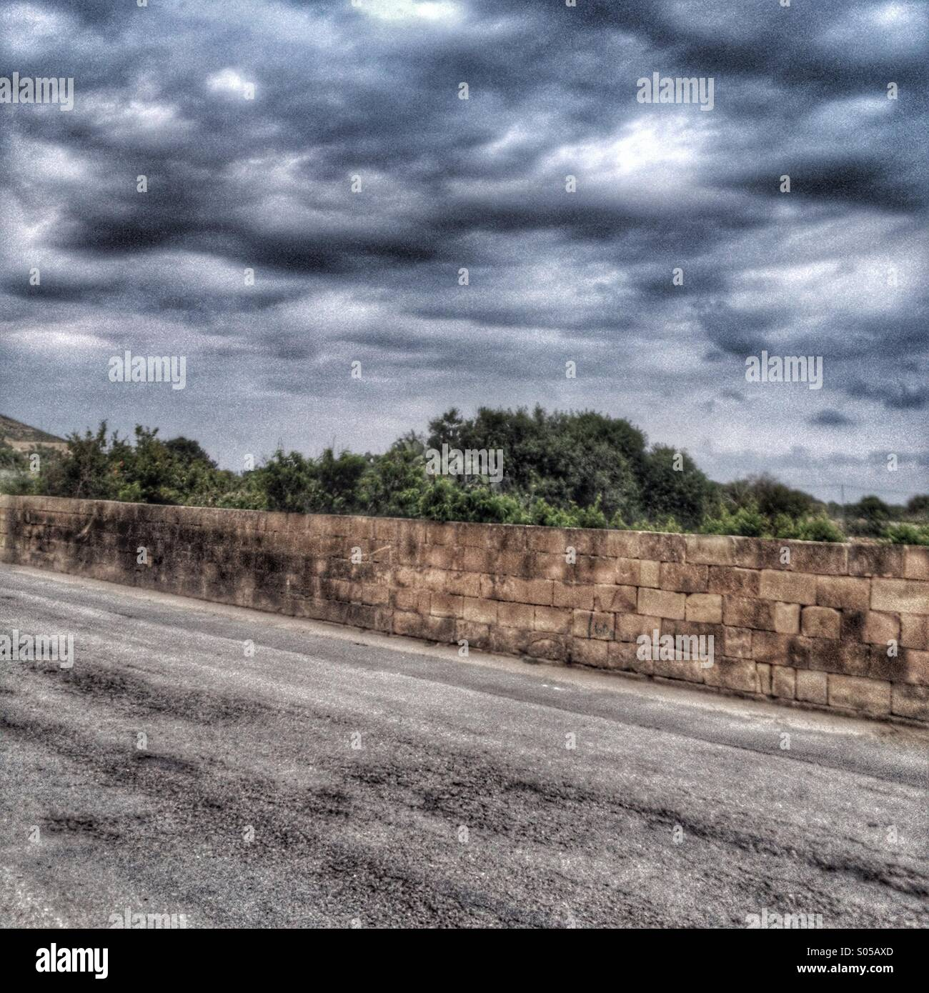 Back road and storm clouds - Stock Image