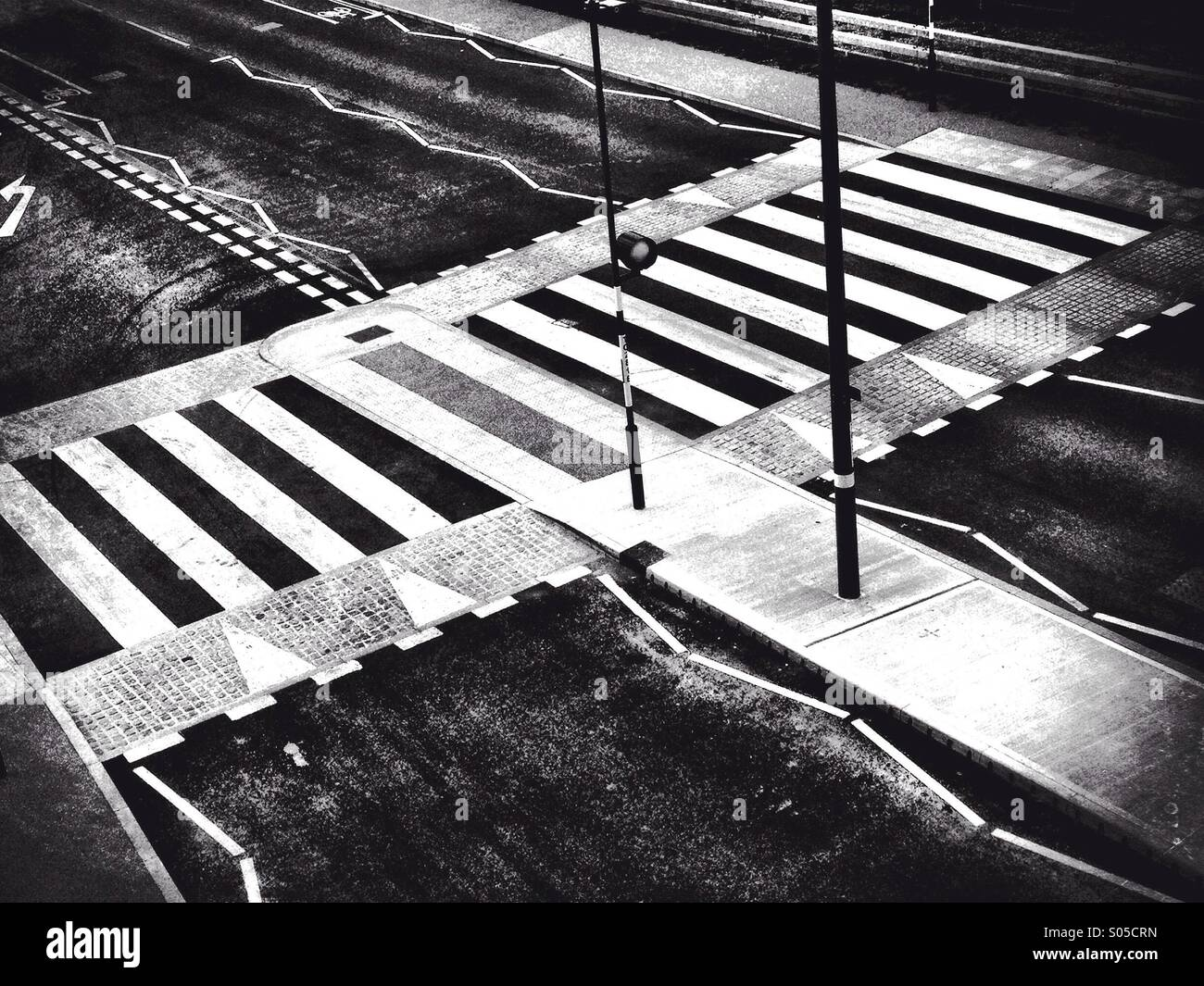 Zebra Crossing on a wide empty road. Black and white photograph. Stock Photo
