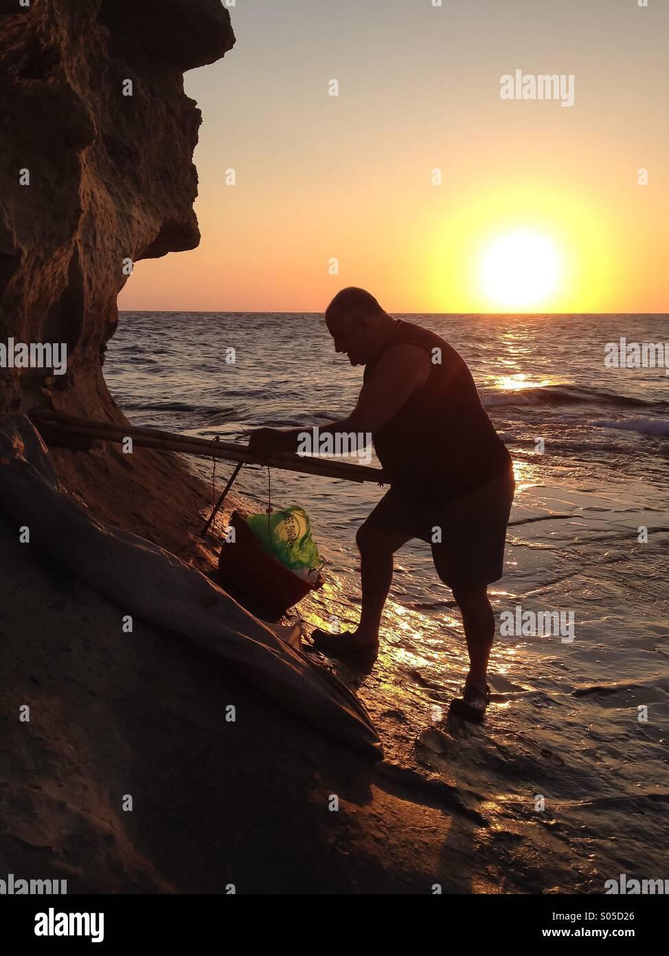 Fisherman preparing float and sail at dawn - Stock Image