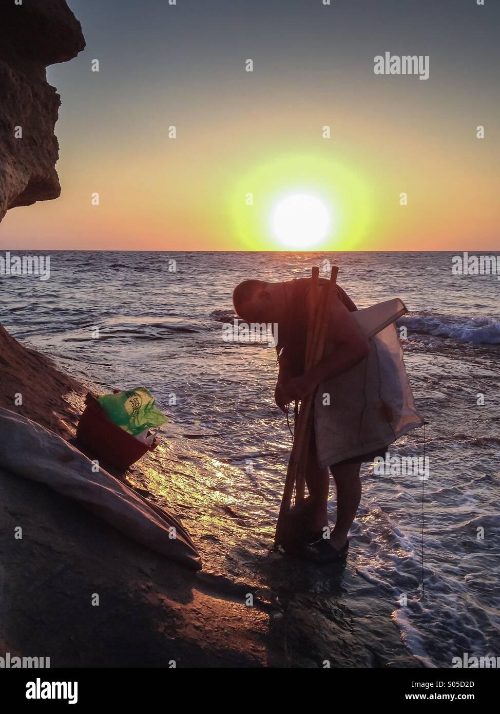 Fisherman at dawn preparing traditional float and sail - Stock Image