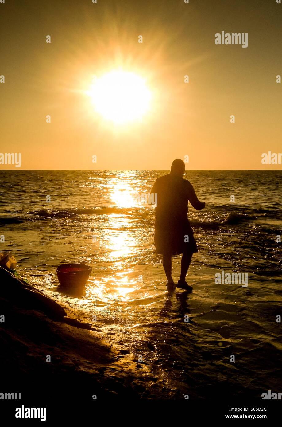 Fisherman tending float line at dawn - Stock Image