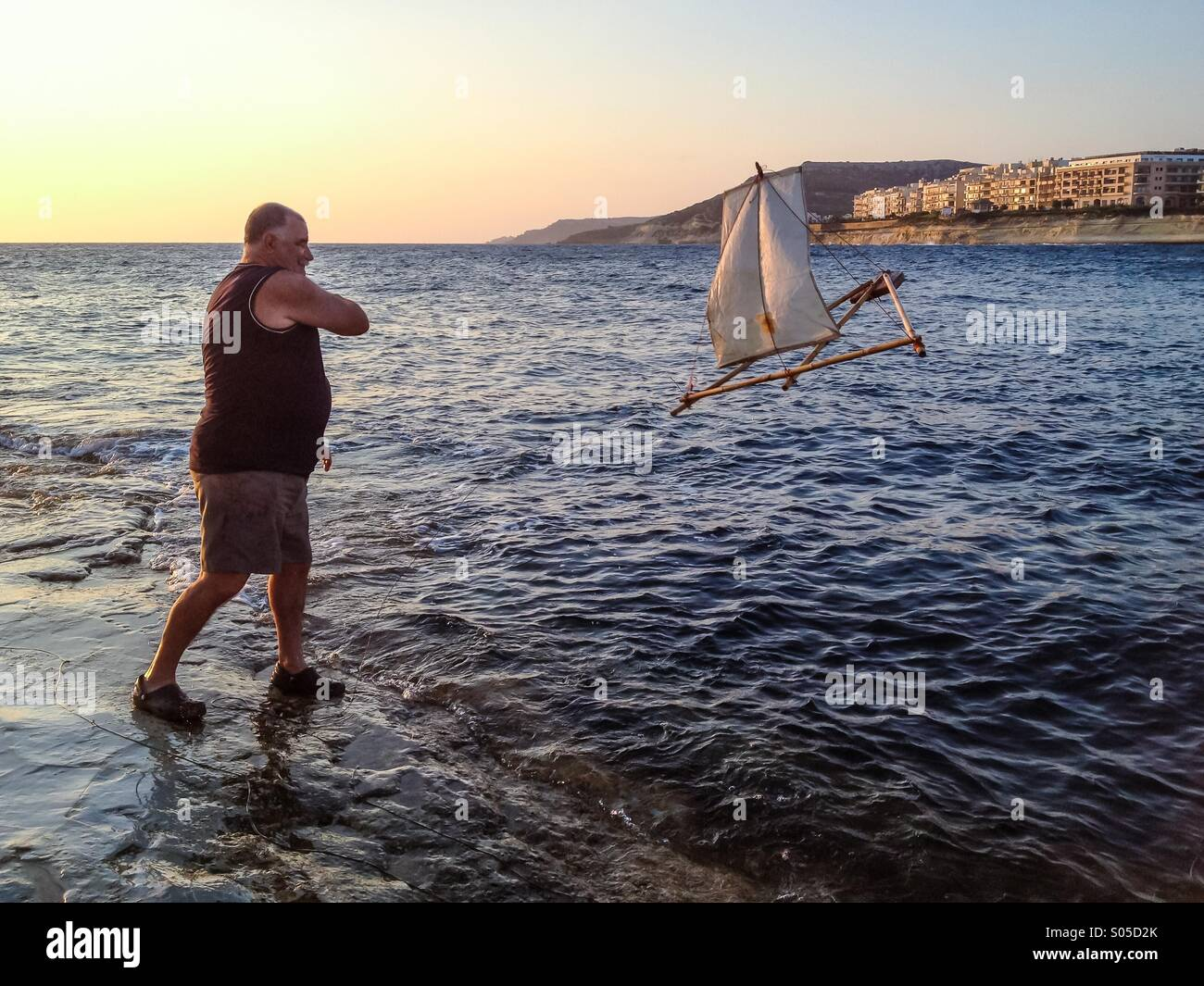 Fisherman launching longline float and sail at dawn - Stock Image