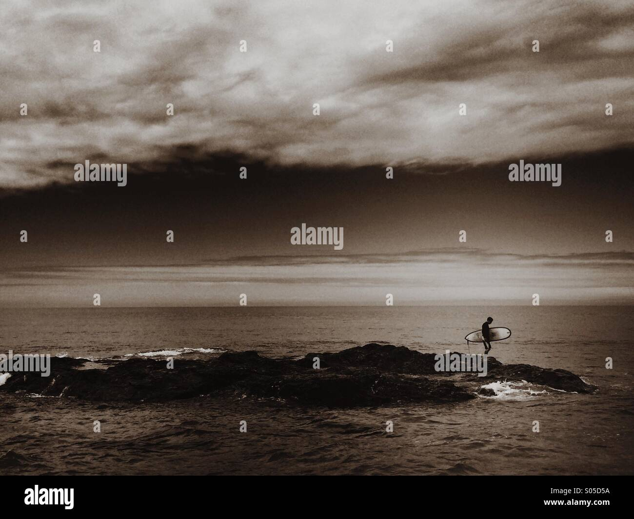 Surfer exploring the coast for waves. - Stock Image