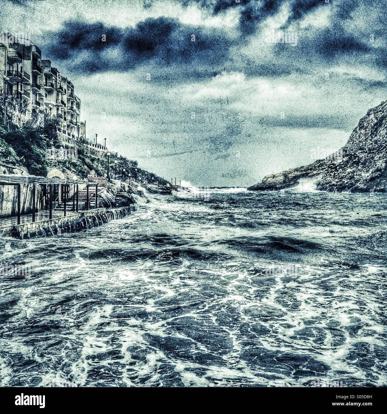Storm seas lashing into small harbour - Stock Image