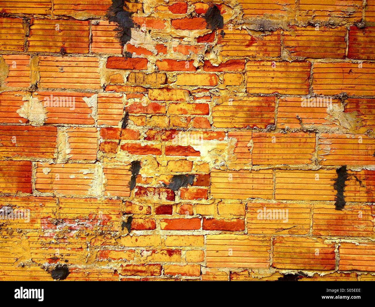 Detail of a colorful orange and yellow brick wall that has been repaired with odd shaped brick on the outside of - Stock Image