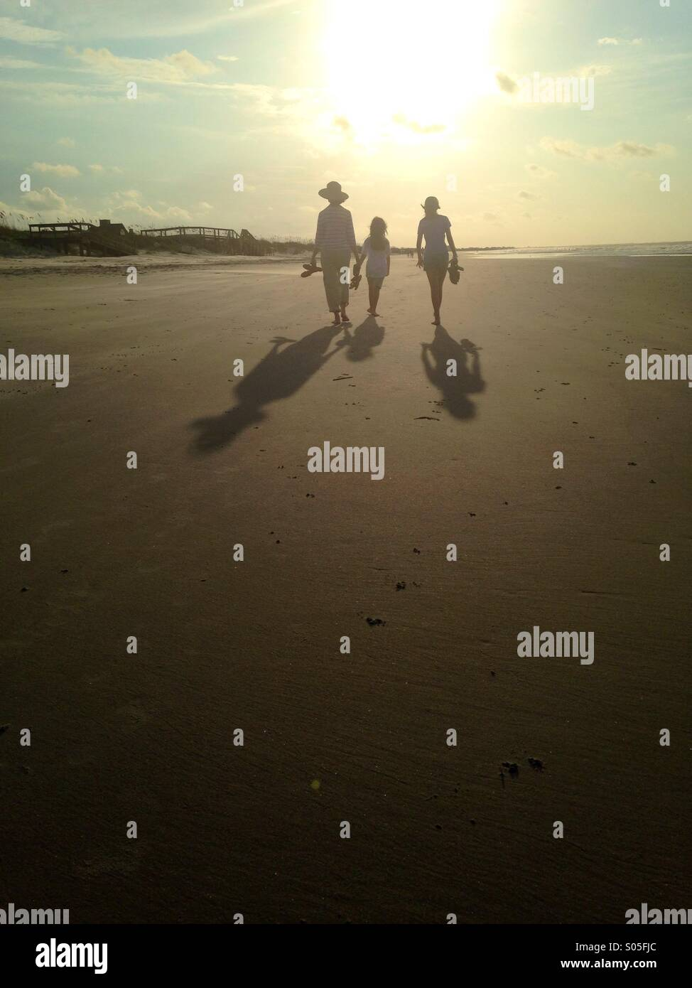 The silhouettes of three people walk along the beach in morning light. - Stock Image