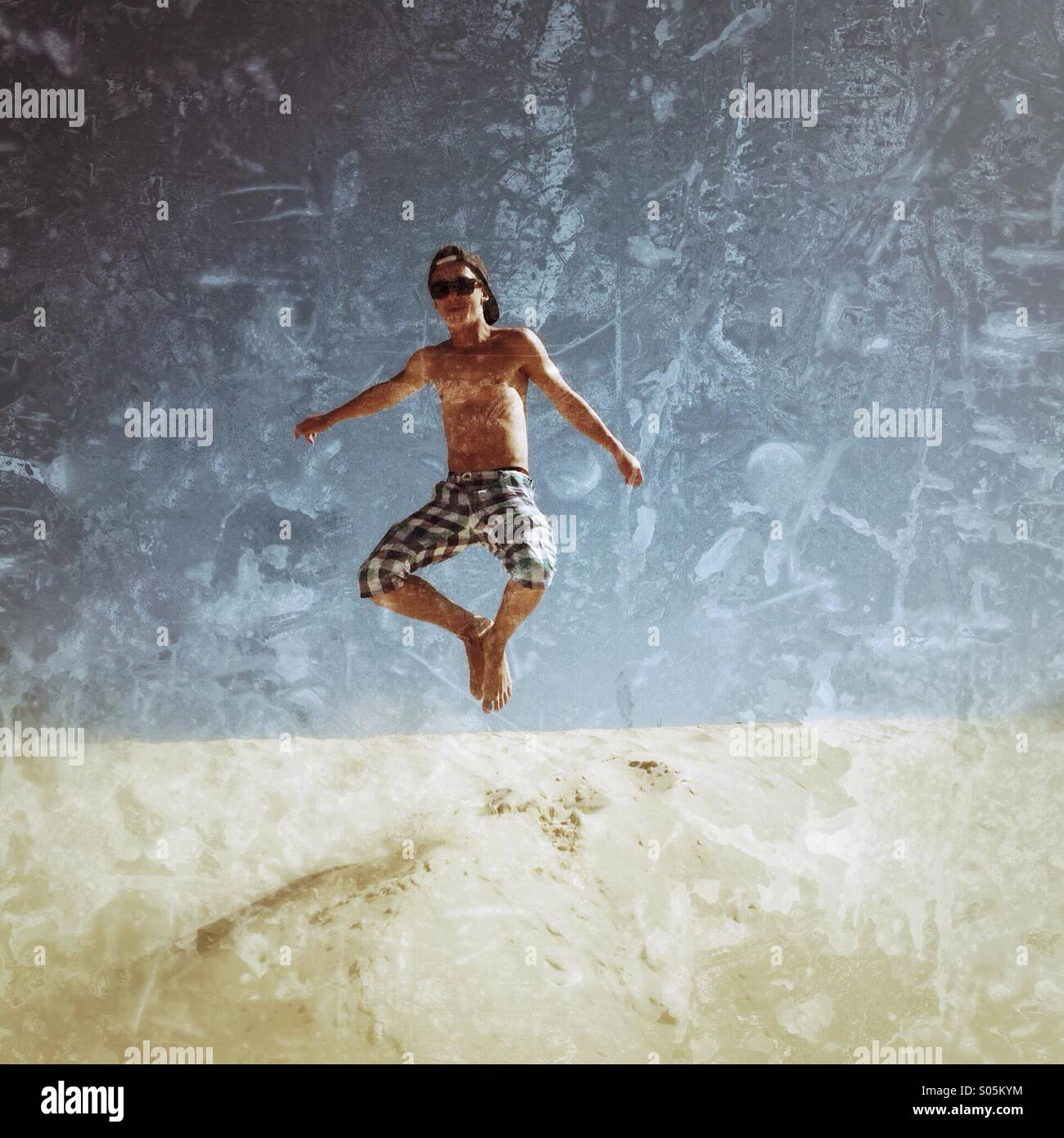 Boy jumping in Tarifa dunes. - Stock Image