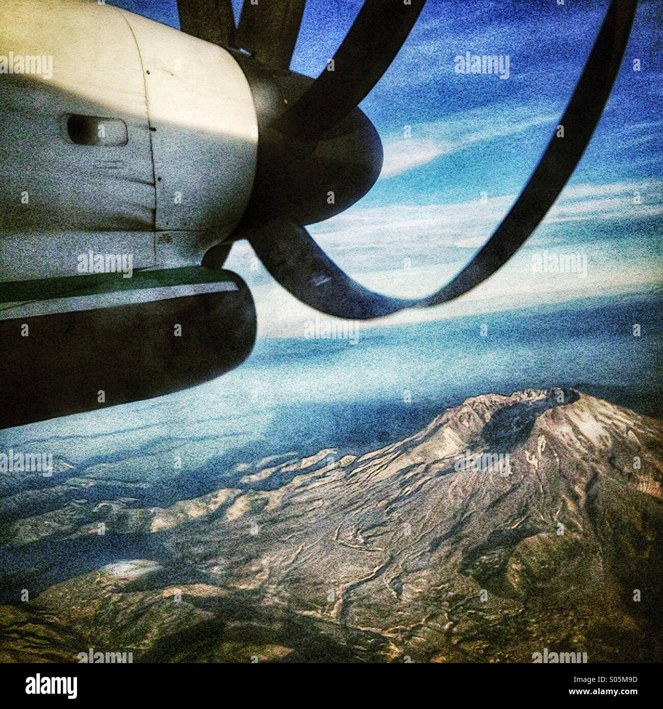 Turbo Prop airplane flying over Mt ST Helens with Mt Hood in the distance. - Stock Image