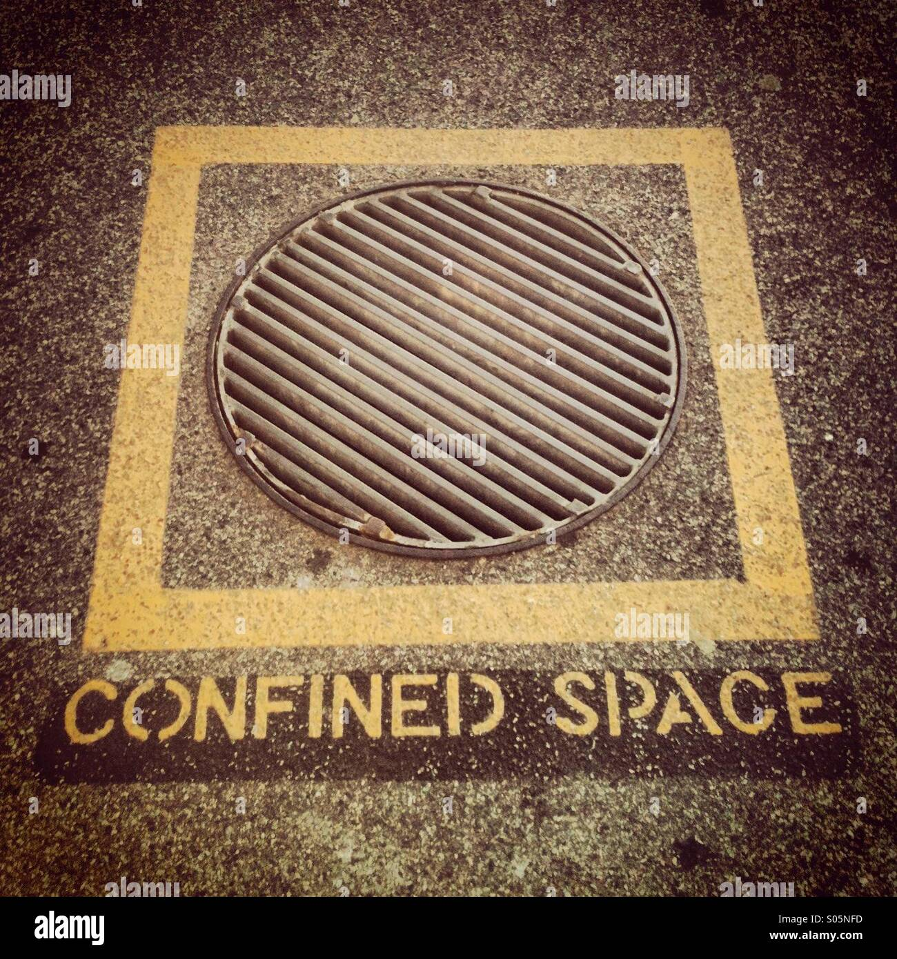 Confined space stencilled onto the floor below a yellow square and drain cover - Stock Image
