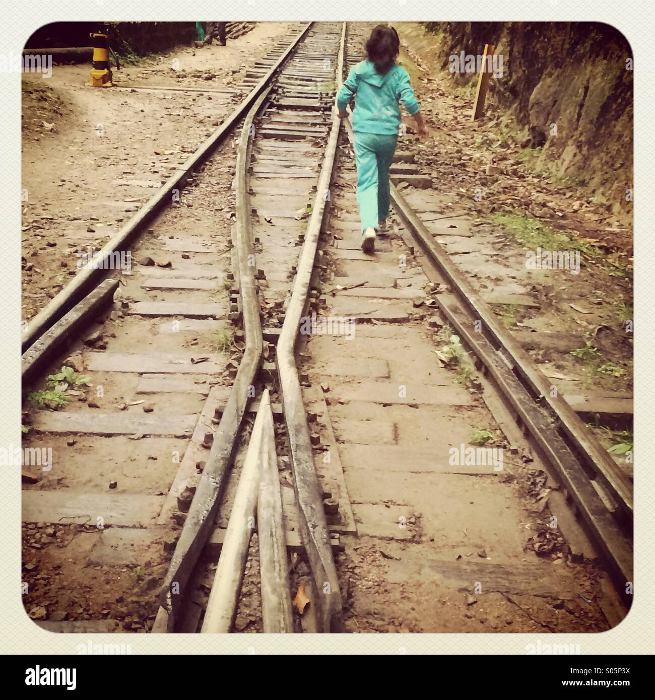 Girl walking on the train lines 2014 - Stock Image