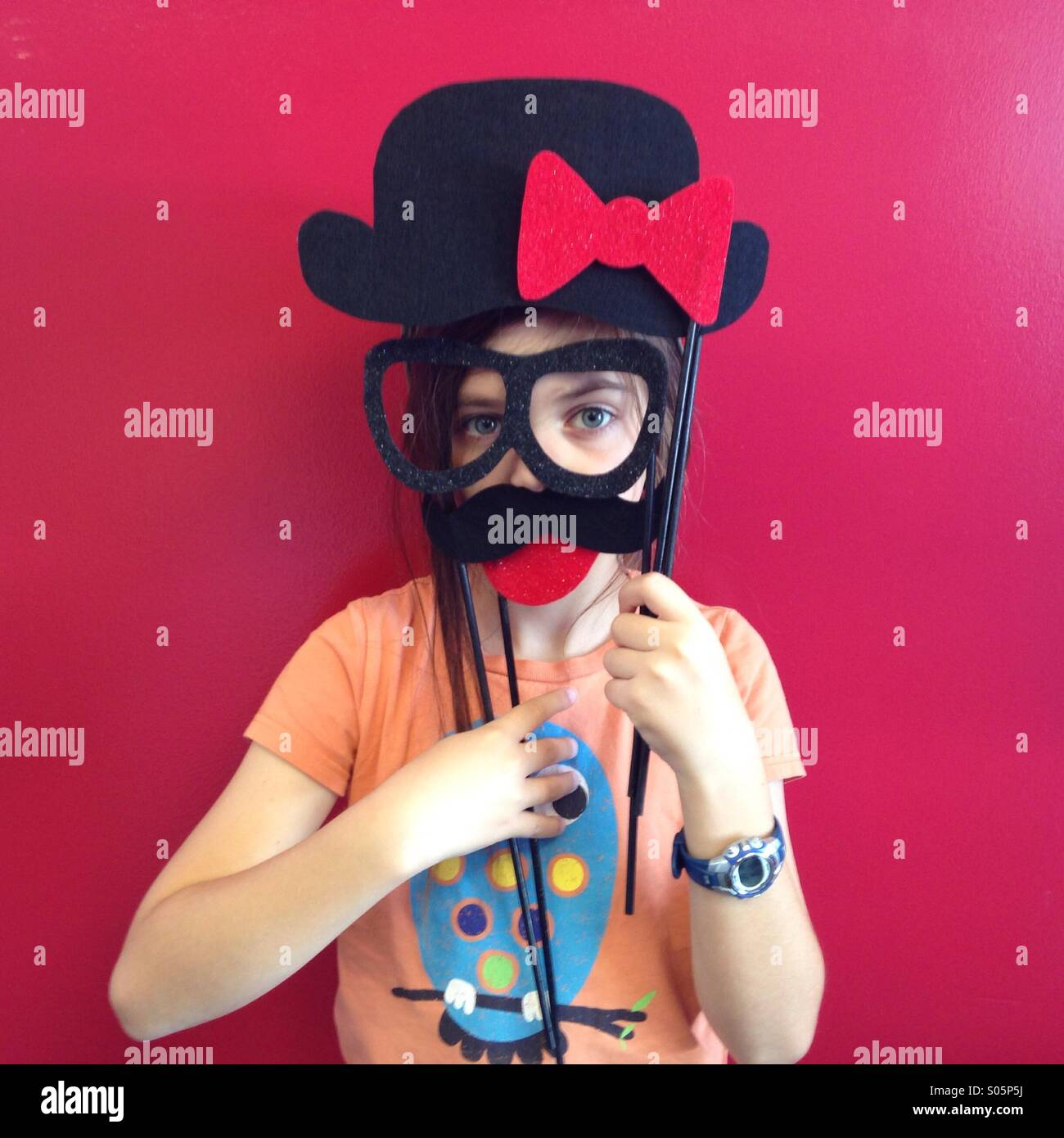 Silly kid wears fake glasses and a mustache against a red wall. - Stock Image