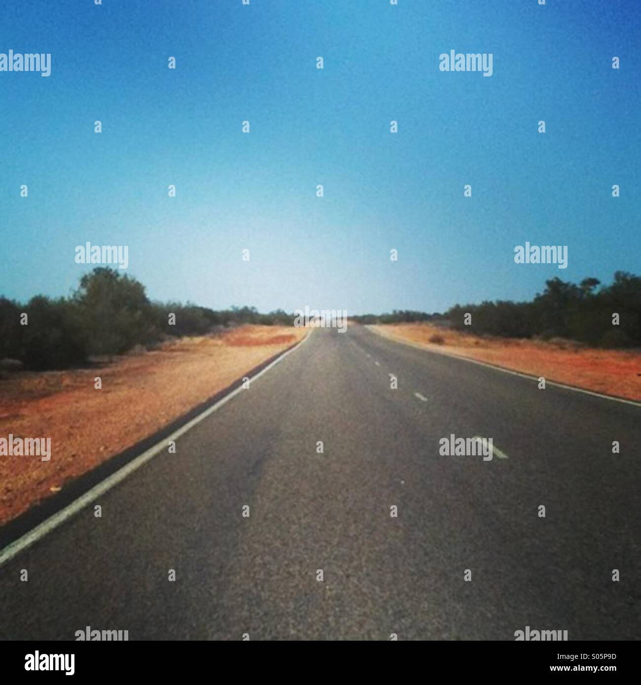 Long and straight road in the Western Australian outback - Stock Image