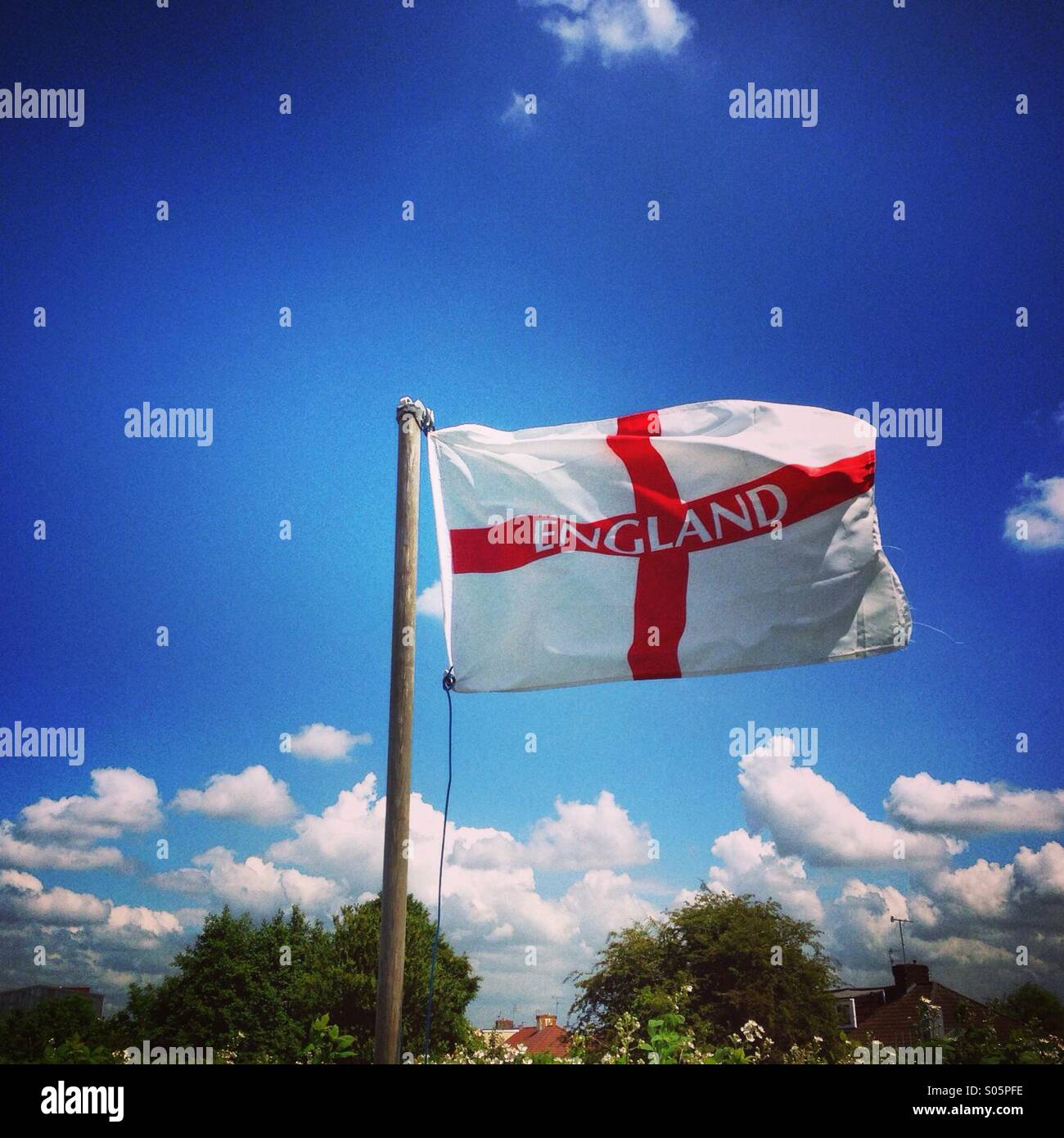 England Flag of St George flying against a blue sky Stock Photo