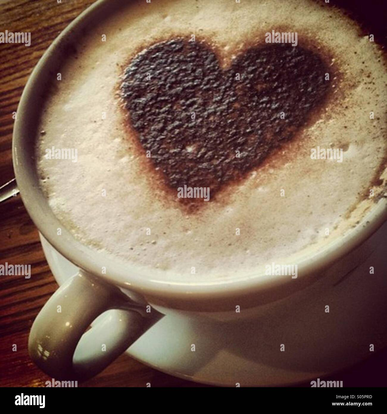 Cappuccino coffee drink in large mug and a heart shaped chocolate shape on the foam - Stock Image