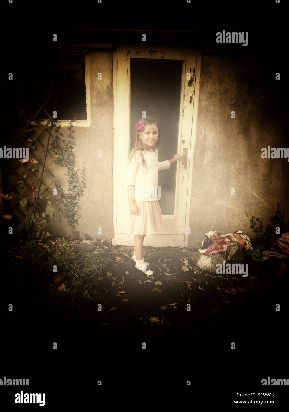 Girl opening door - Stock Image