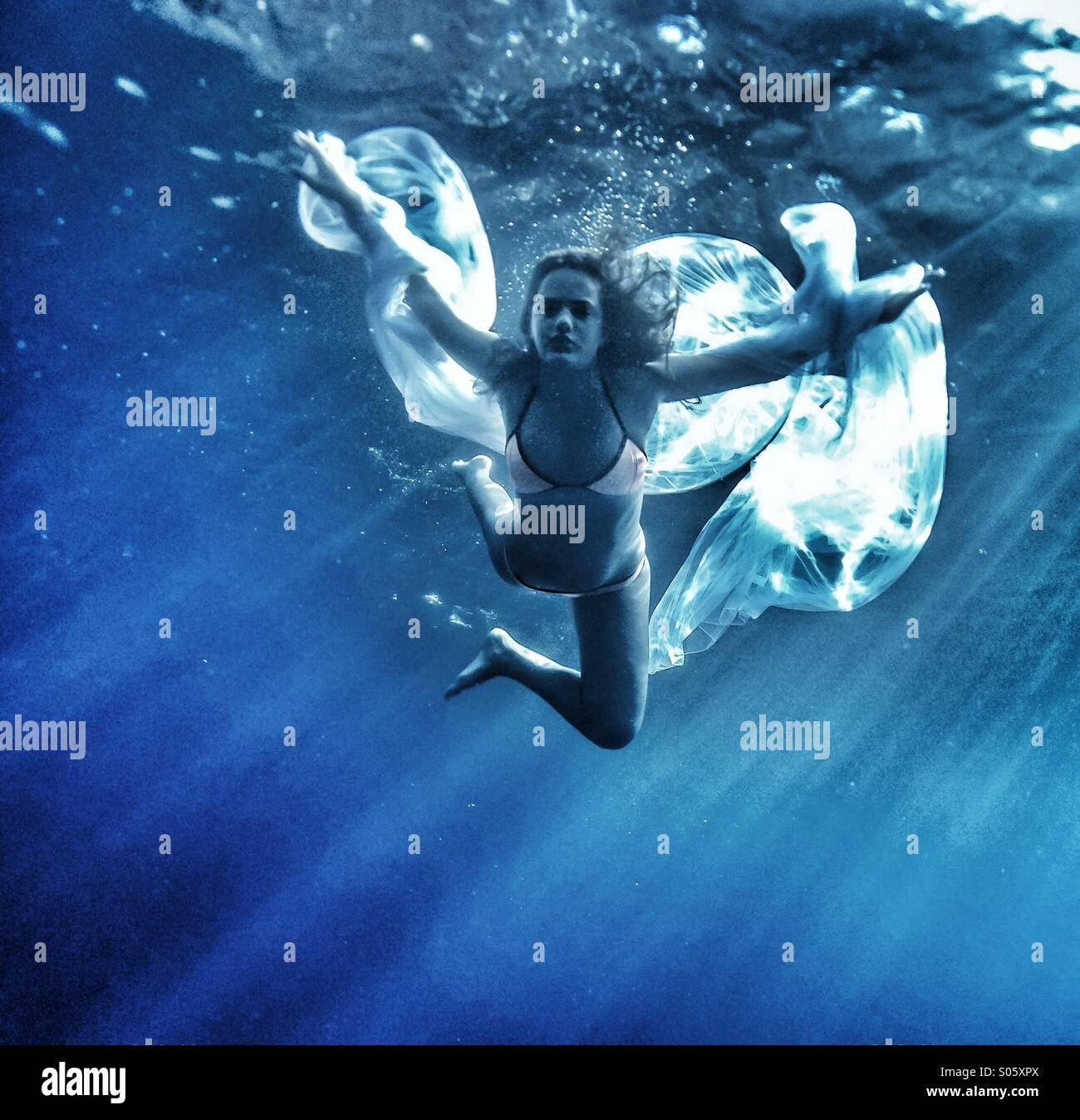 Teenage girl swimming underwater with large white net and orange bikini - Stock Image
