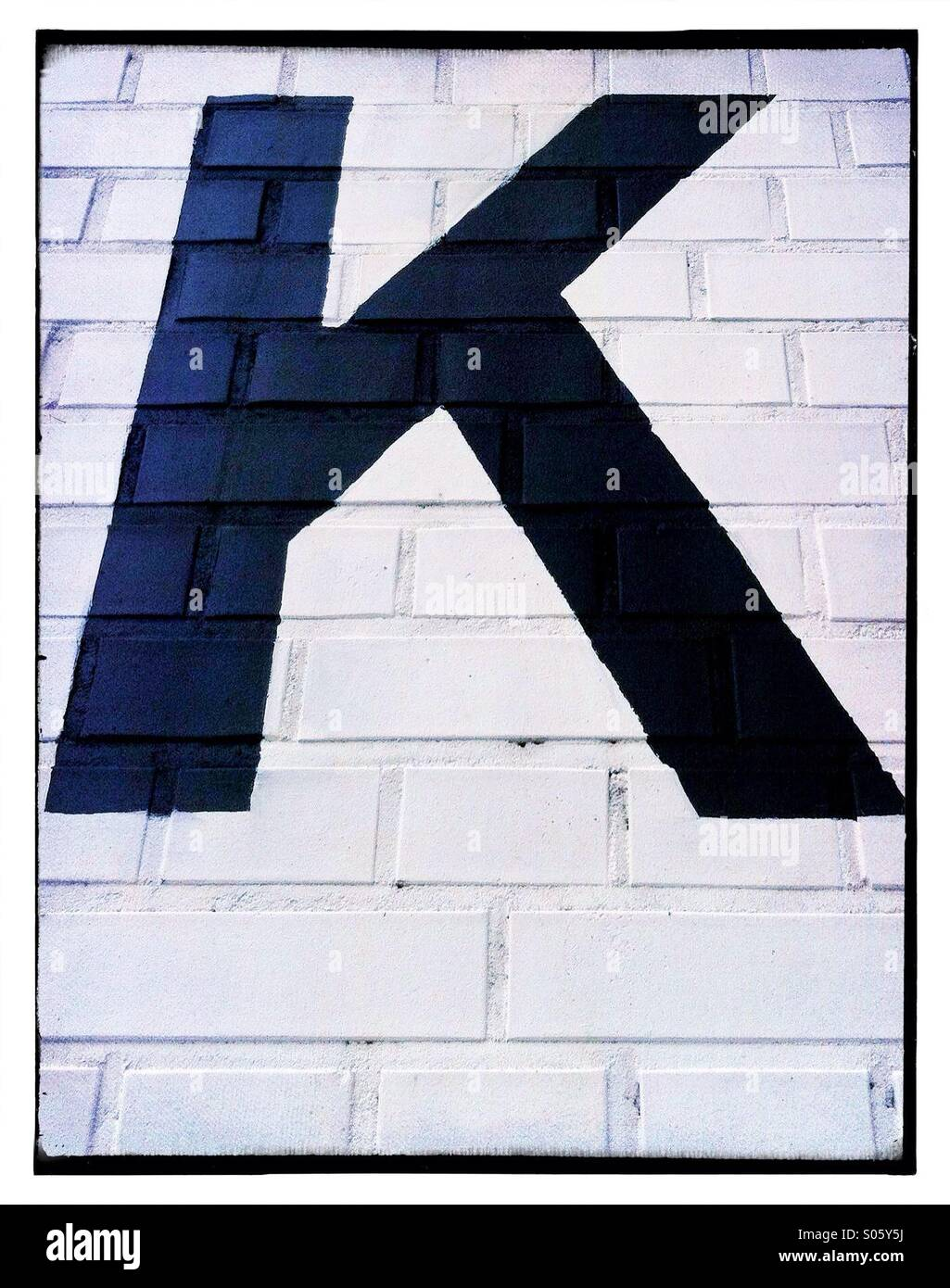Letter 'K' painted on brick wall - Stock Image