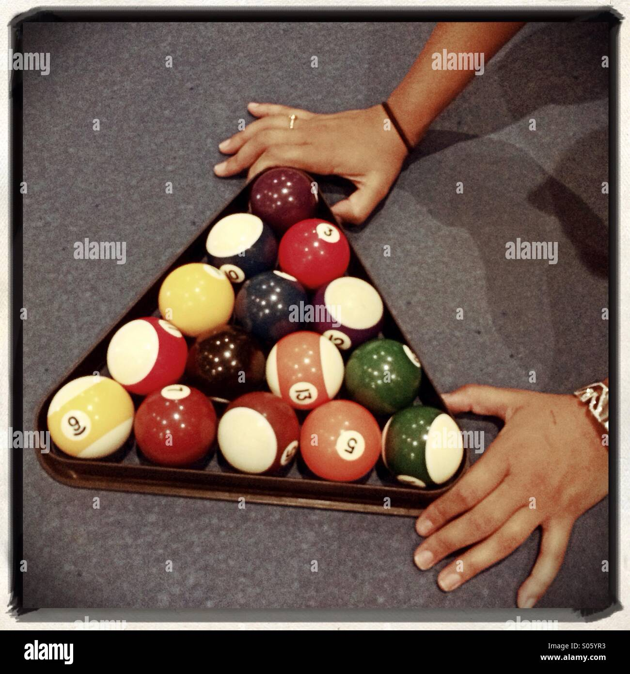 Woman arranging pool balls at the start of a game - Stock Image