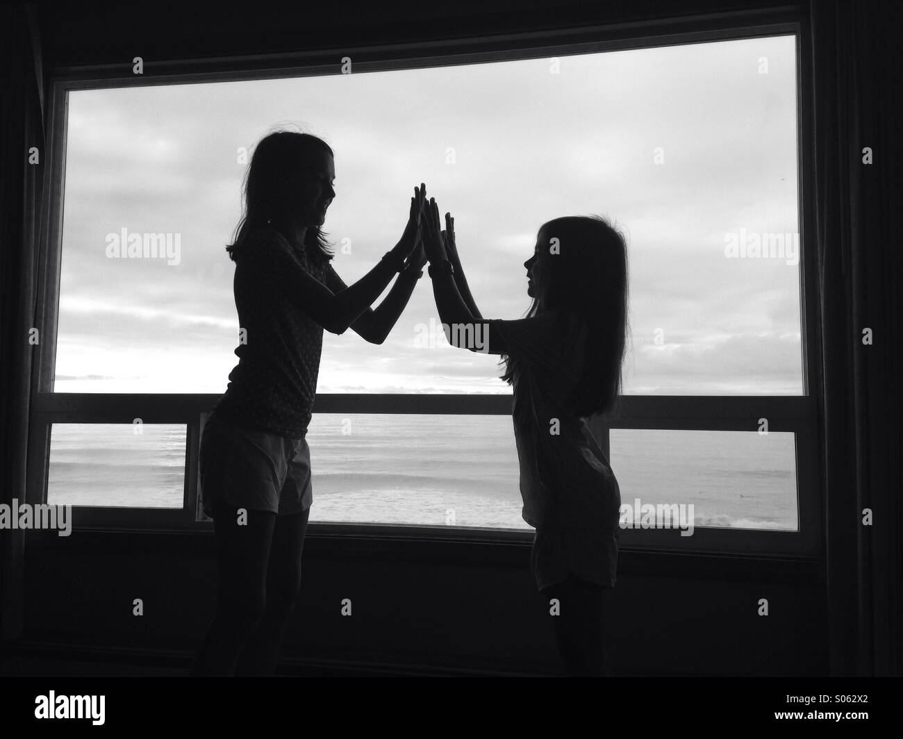Two girls in silhouette high five in front of a picture window. The image is black and white. - Stock Image