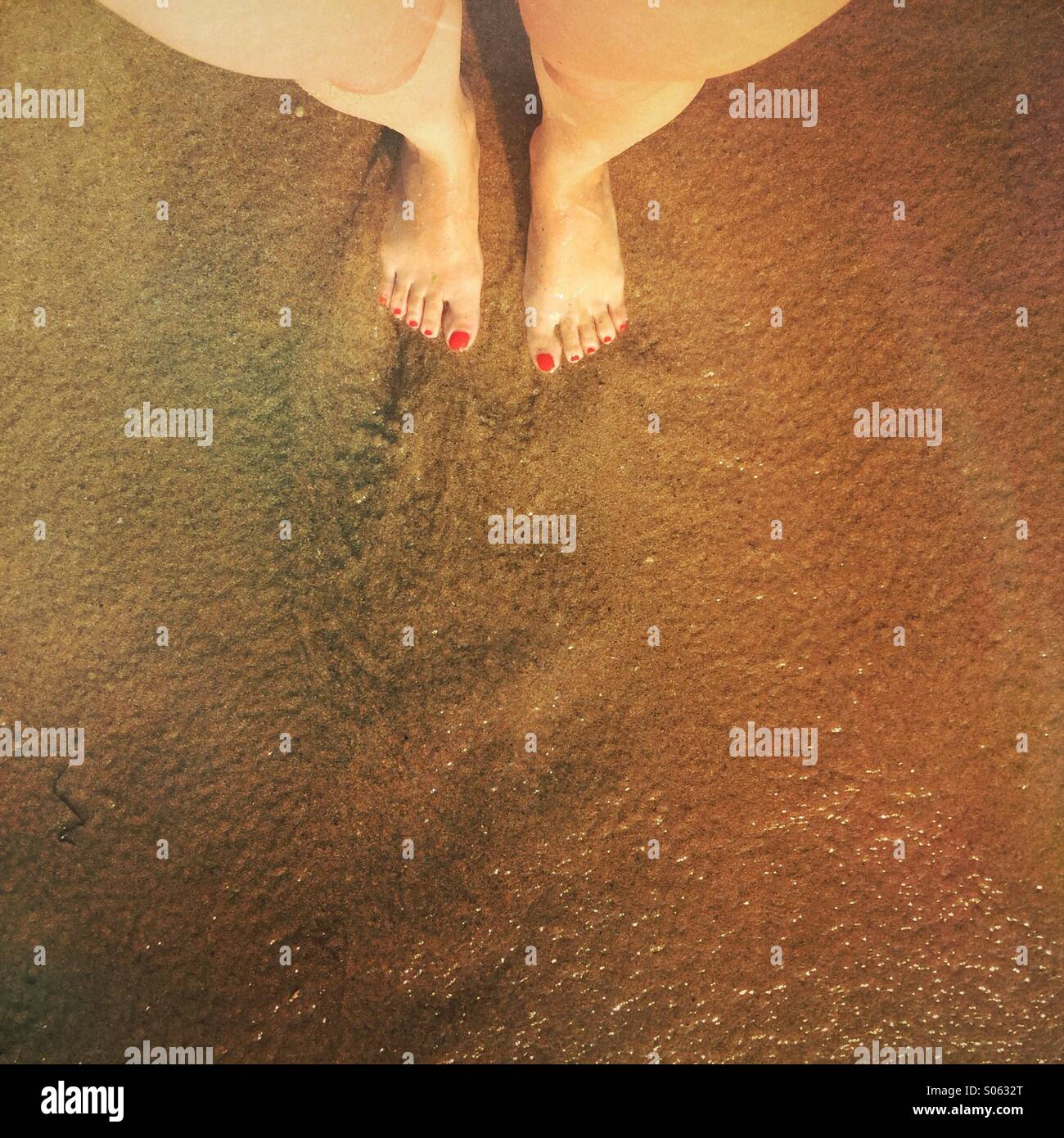 Woman's feet by the shore - Stock Image