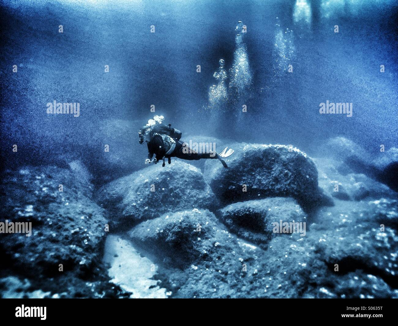 Young female scuba diver diving deep - Stock Image