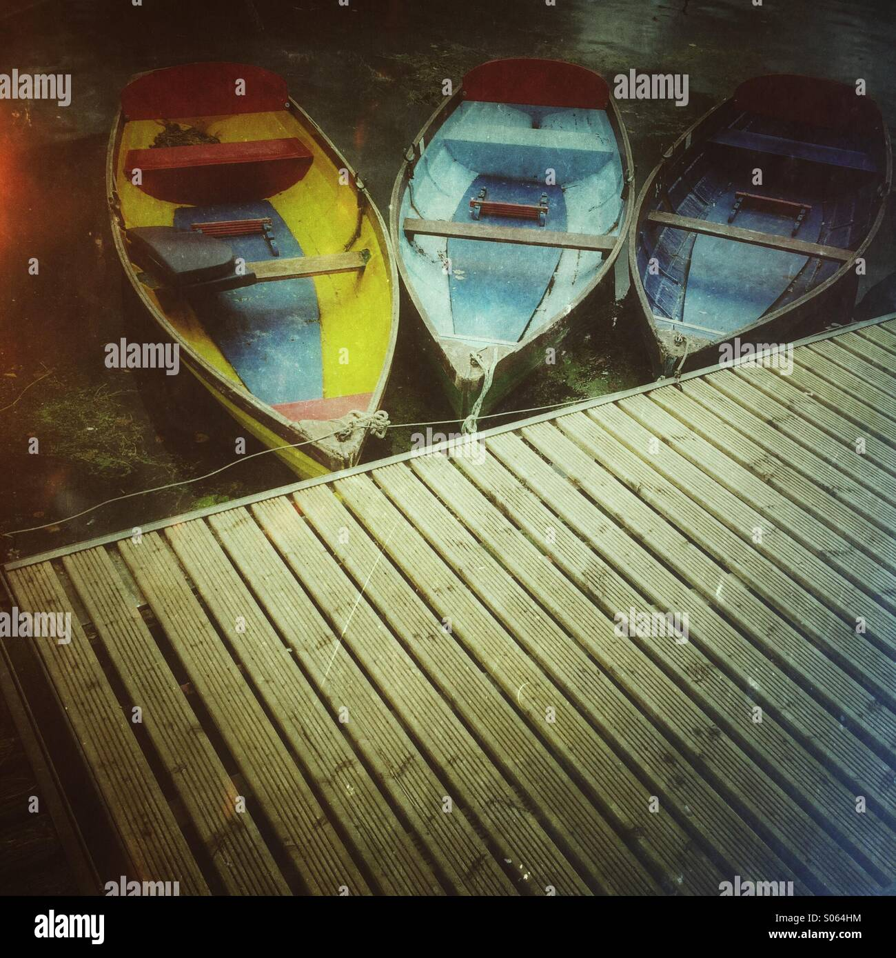 Three colourful rowing boats tied up onto a wooden jetty Stock Photo