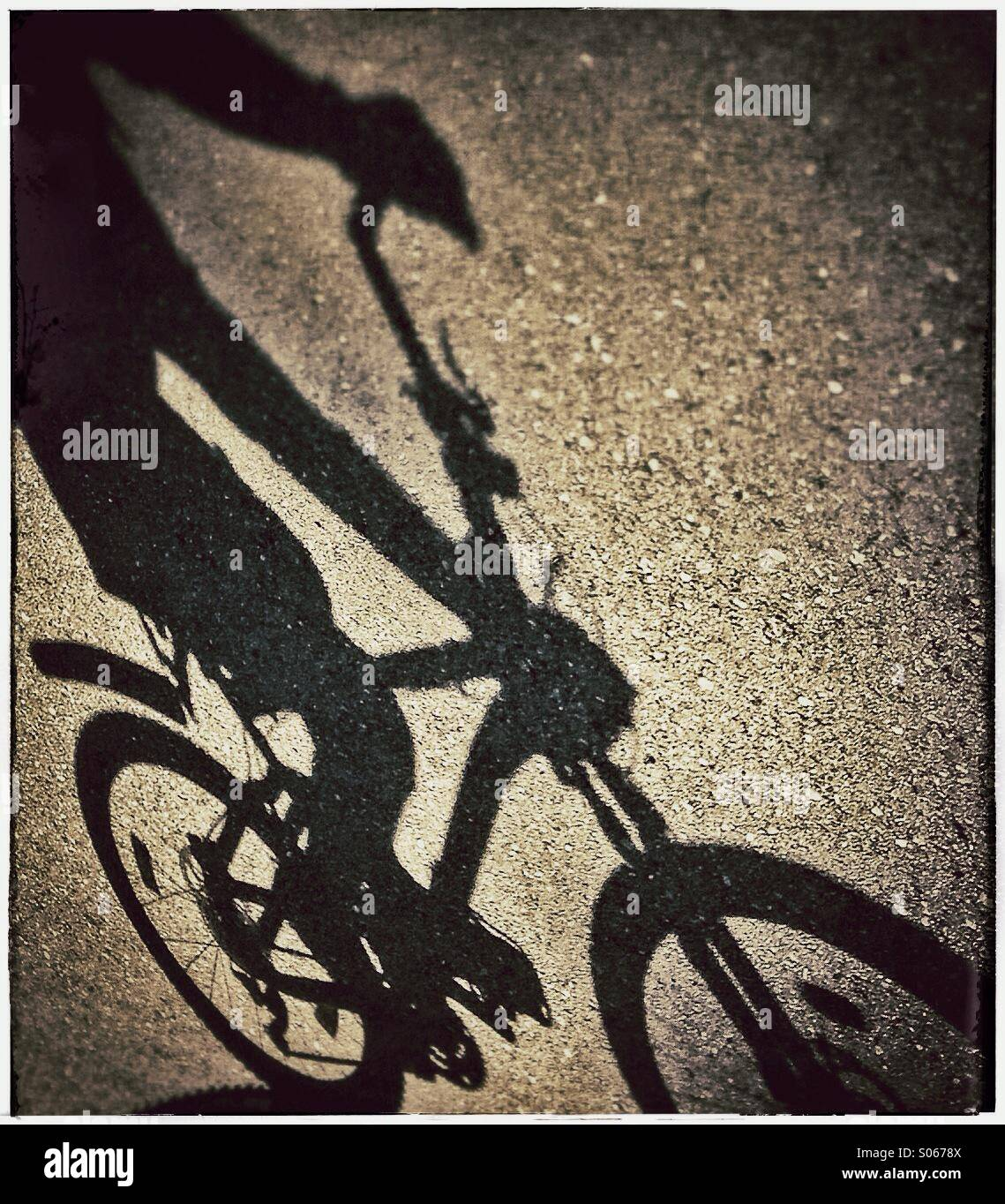 Shadow of somebody riding a bicycle - Stock Image