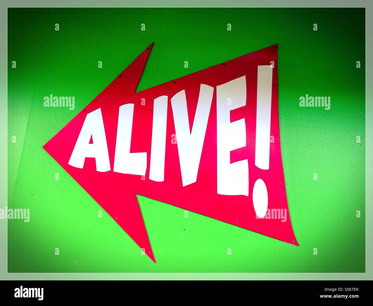 A sign that reads 'alive!' - Stock Image