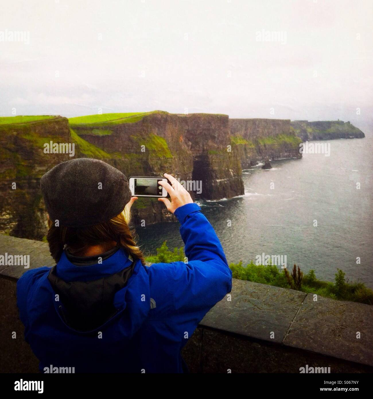 A woman taking a photo of the cliffs of moher. County Clare, Ireland  Europe. - Stock Image