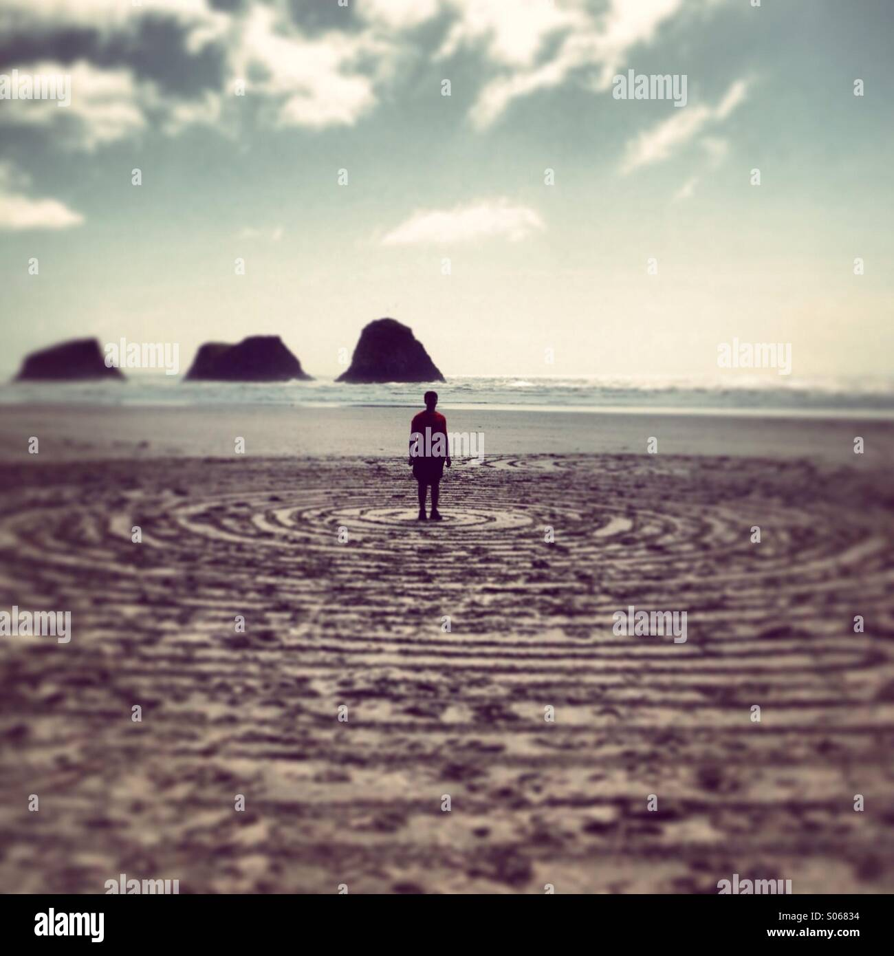 Boy in concentric circles on the beach - Stock Image