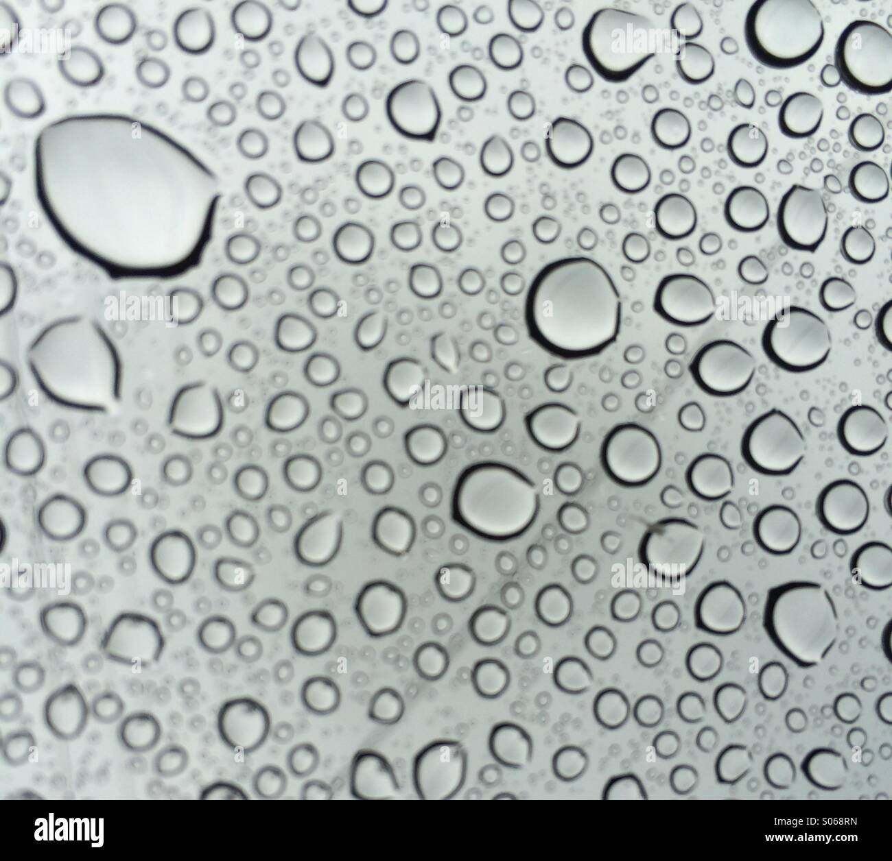 Seattle sunroof. Looking up through the raindrops to the grey summer sky. - Stock Image