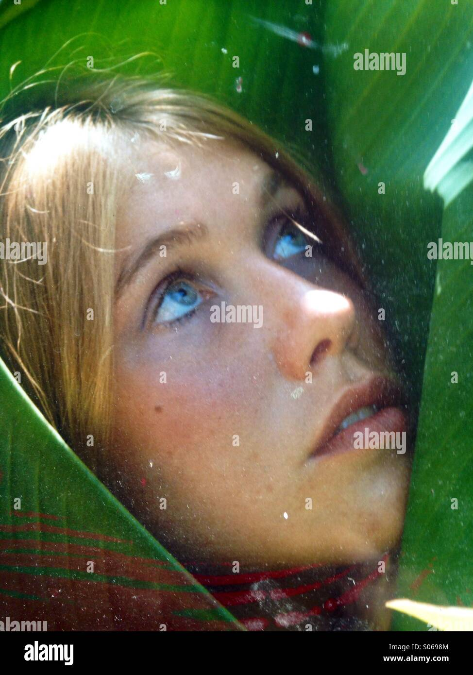 Vertical Young woman's face looking upwards wrapped in a green banana leaf matching her eyes. Stock Photo