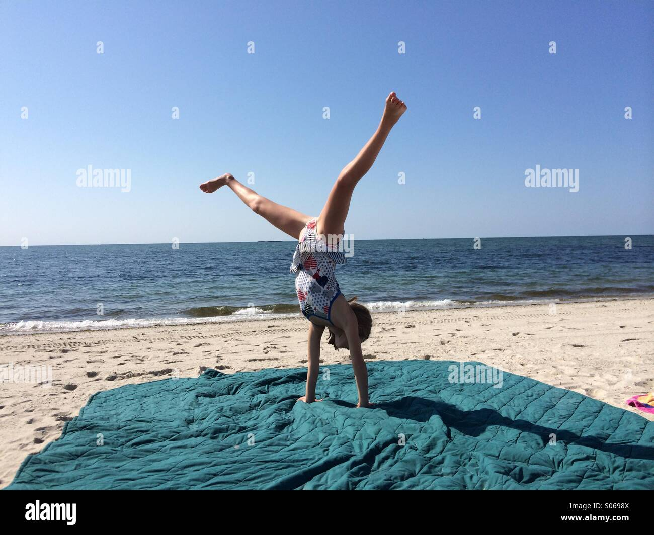 Girls does a cart wheel at the beach - Stock Image