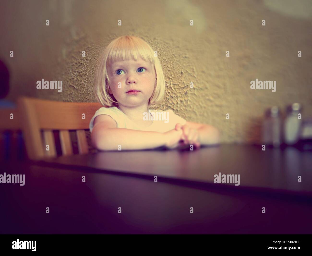 Cute Young blond girl sitting at a table patiently awaiting a meal at a restaurant. - Stock Image