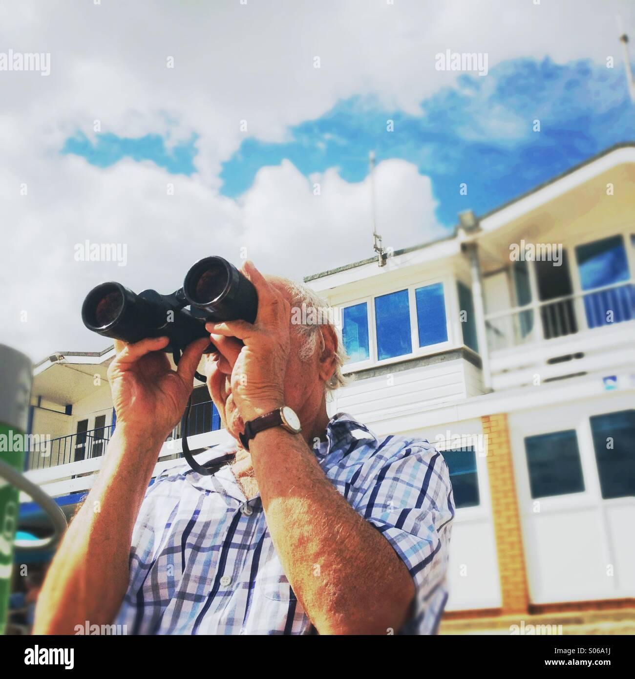 Seaside, binoculars, hobby, seaview, observing, looking, gentleman, elderly, retired, - Stock Image