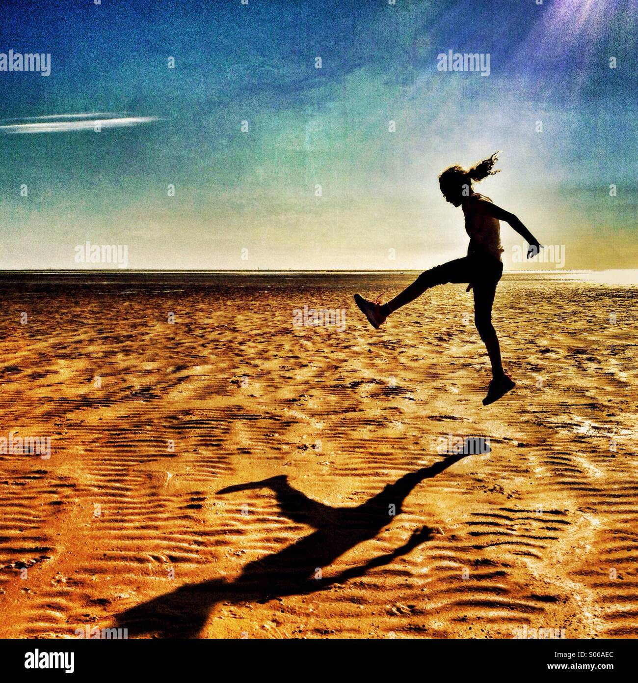 Girl jumping on empty beach - Stock Image