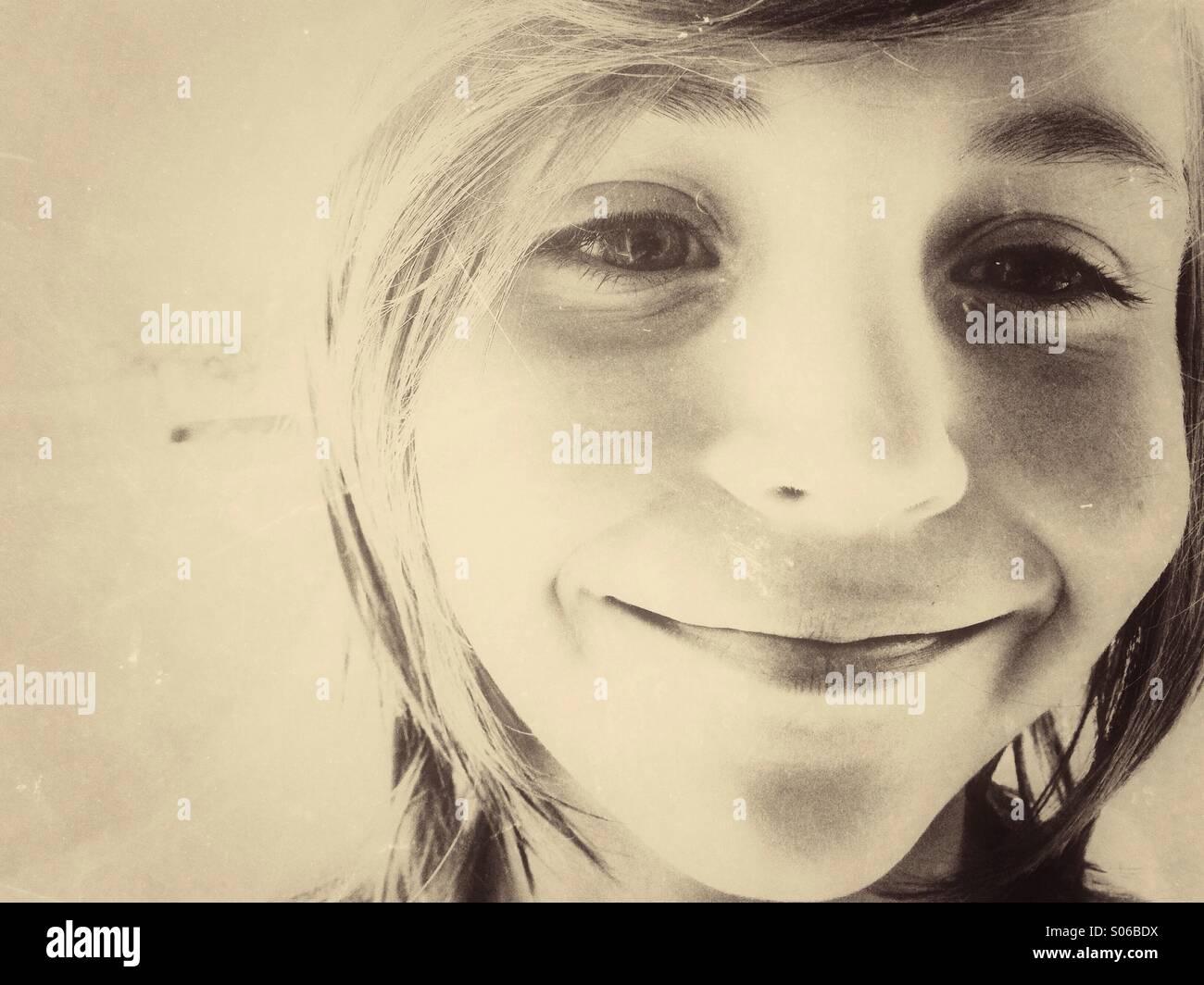 Caucasian boy smiling. Sepia vintage toning. - Stock Image