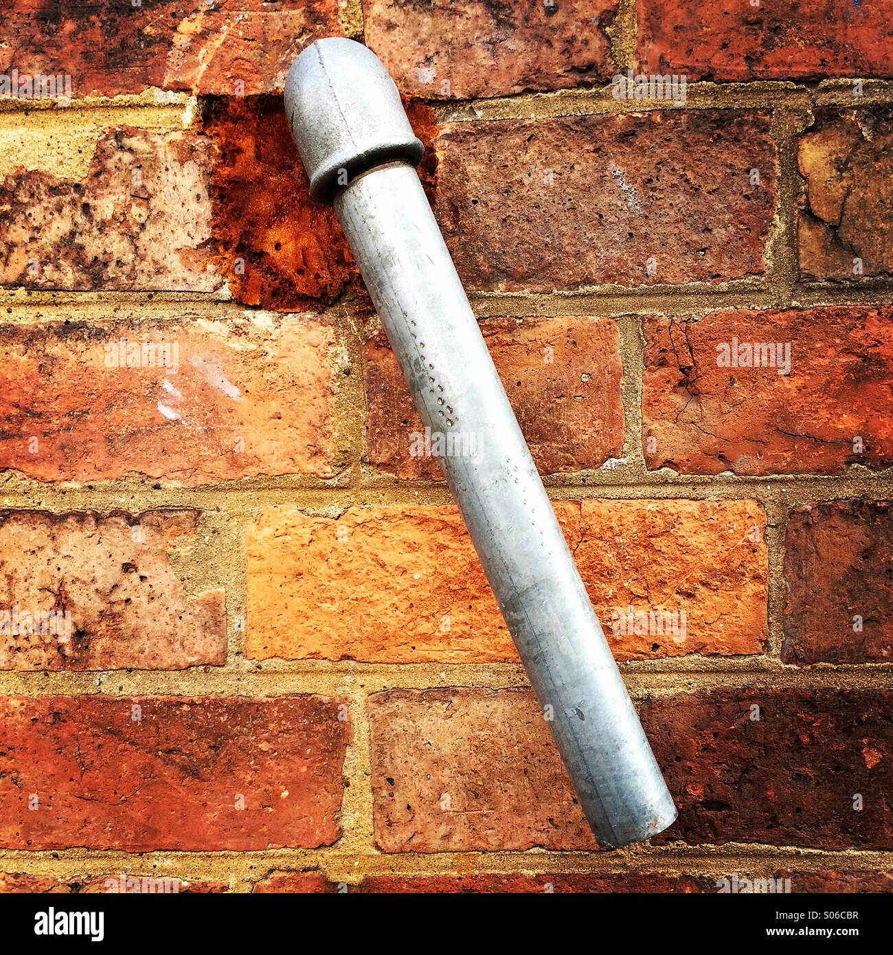 Overflow pipe protruding from a brick wall. - Stock Image