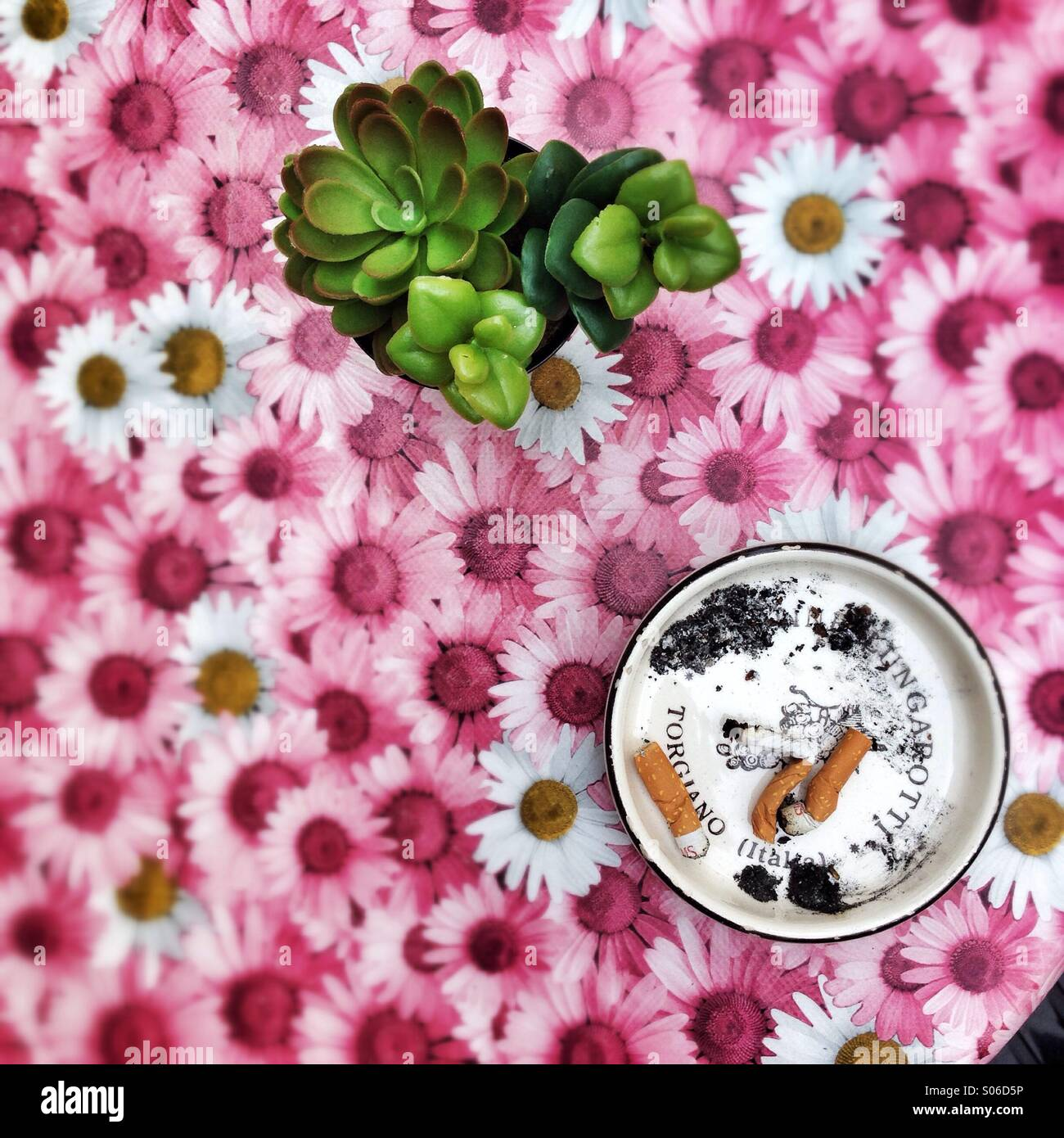 Ashtray on a flowery table cloth in cafe in Italy Stock Photo