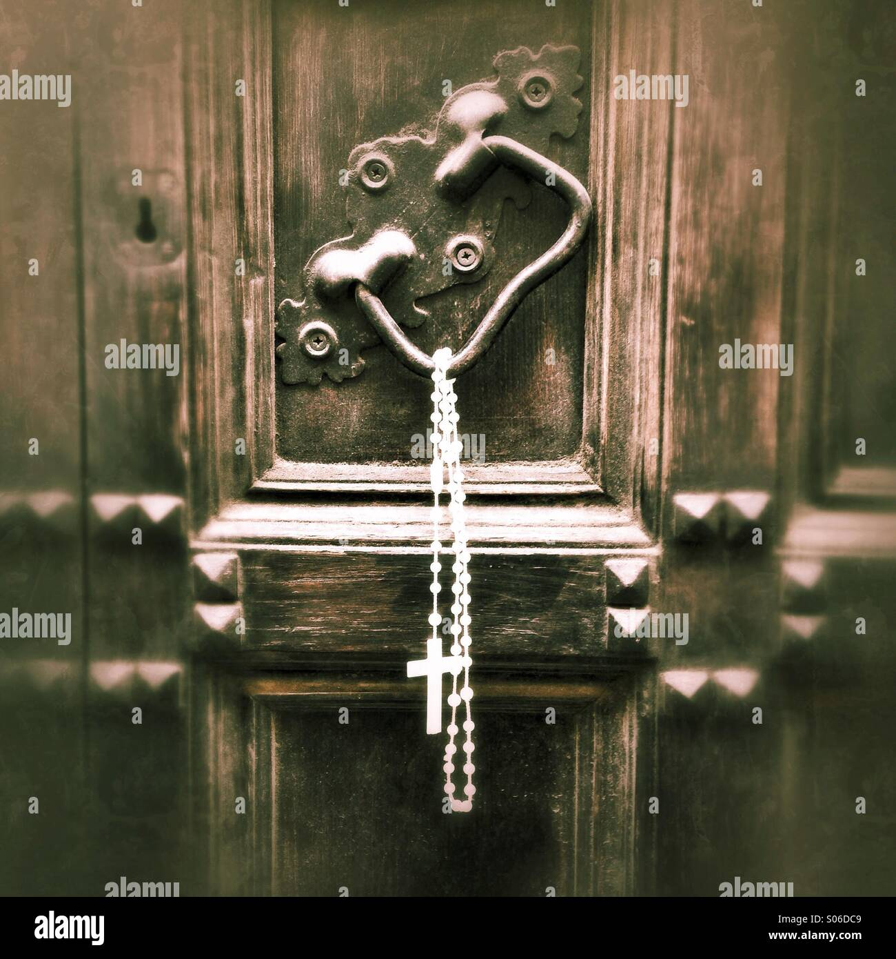Rosary hanging on church door in Italy Stock Photo