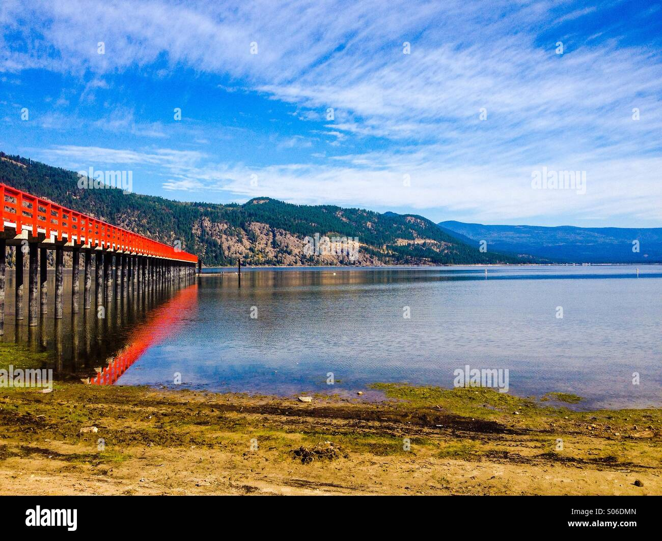 Red pier stretching out into the lake on a late summer day, in Chase, British Columbia. - Stock Image