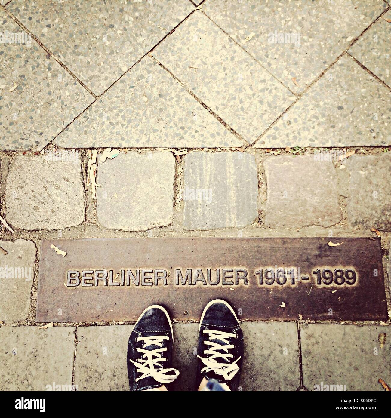 Berlin Wall memorial stones in pavement with feet - Stock Image