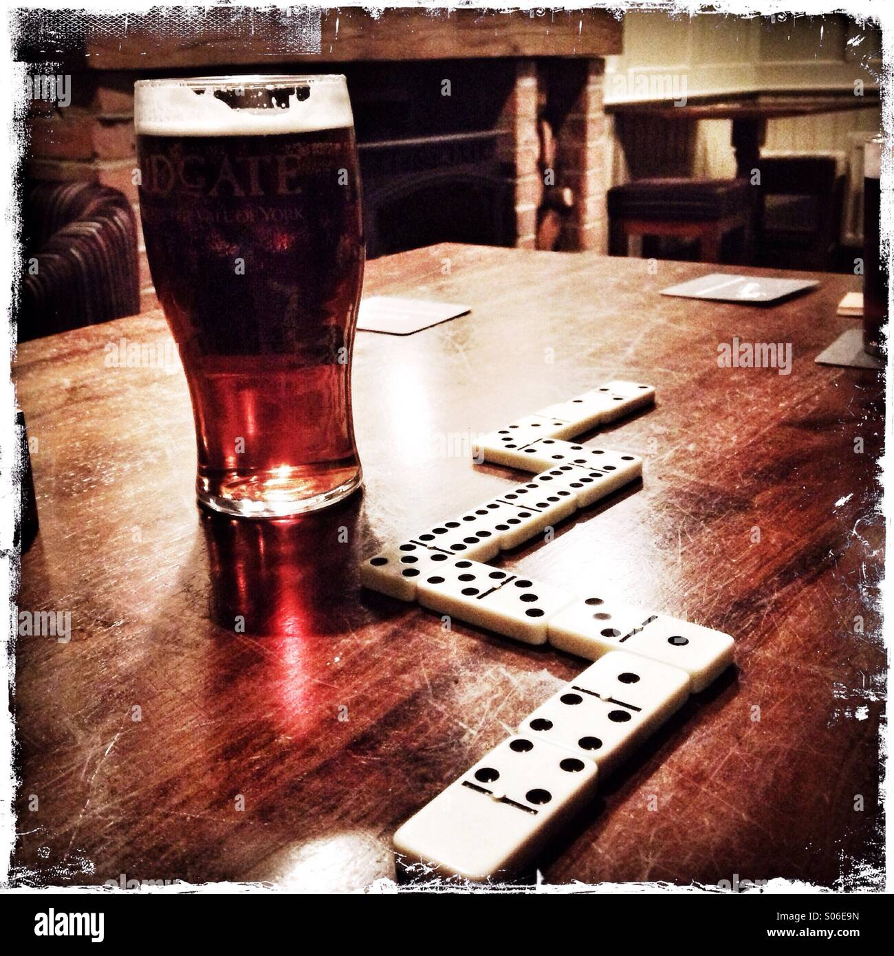 A pint and a game of dominos. - Stock Image