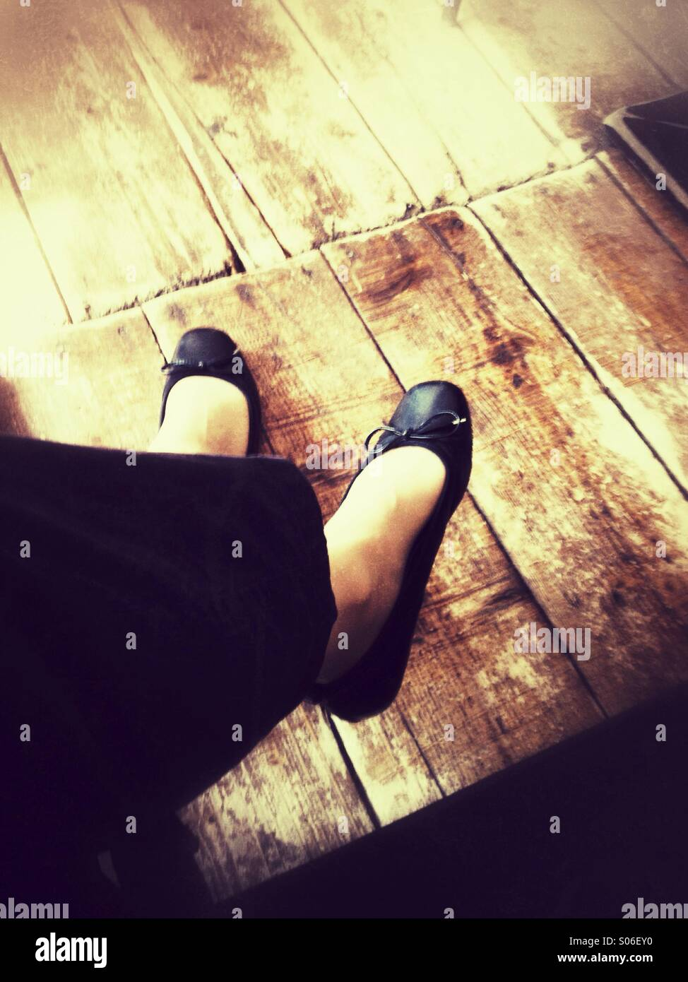 Woman's feet under the table above an Old wooden floor. Retro styled postprocessing. - Stock Image