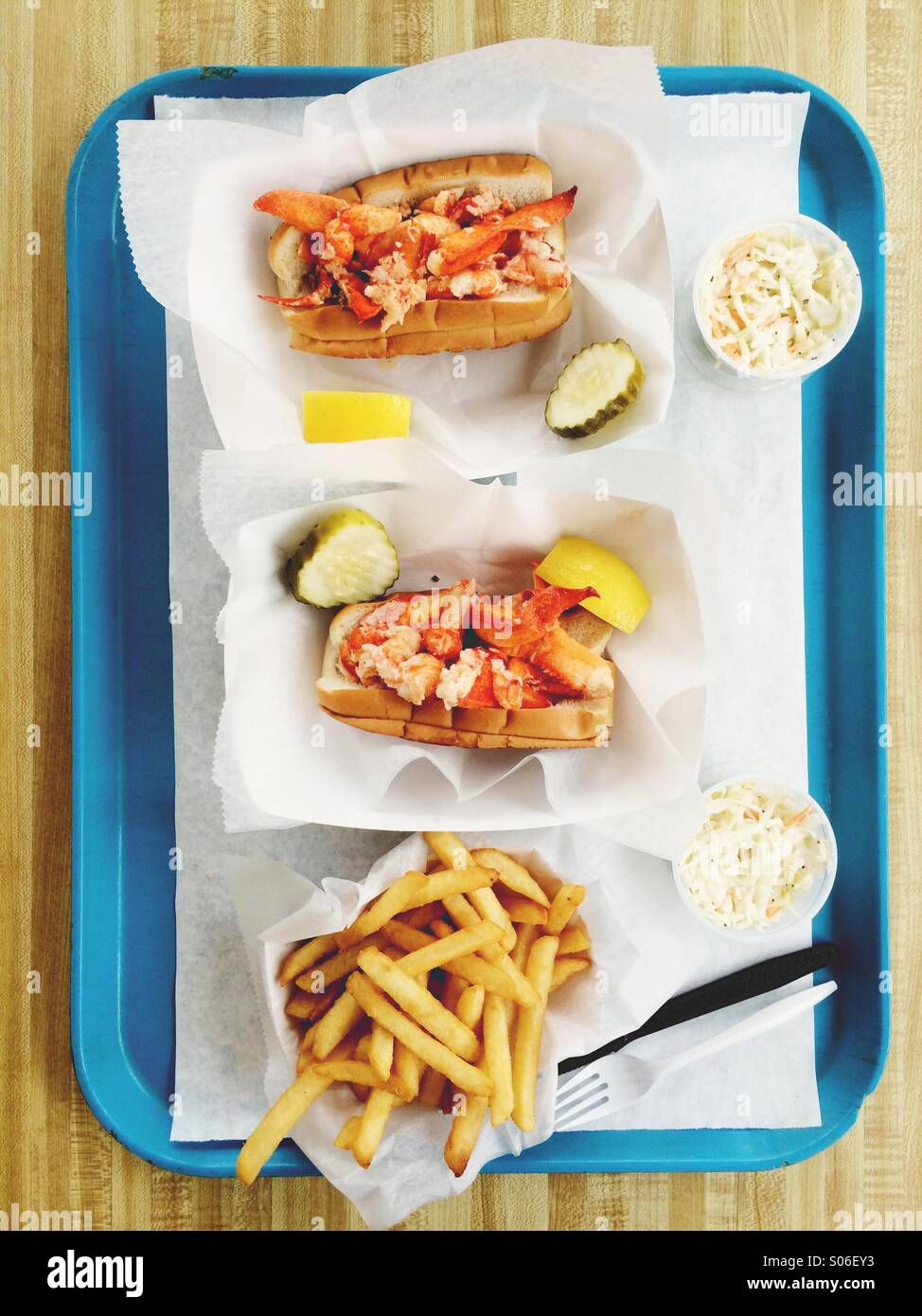 Classic New England lobster rolls, on a tray with fries and coleslaw. - Stock Image