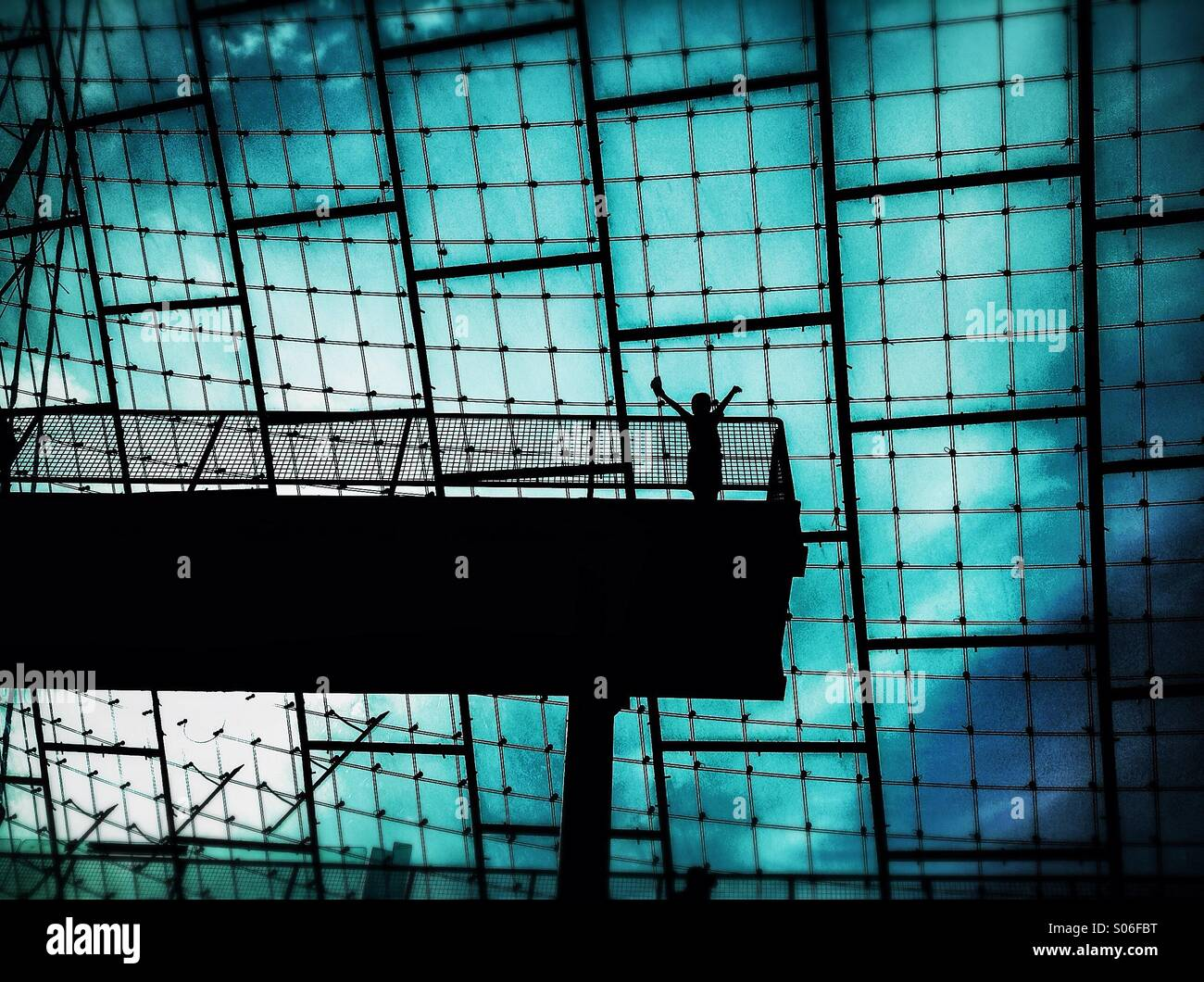 Silhouette of a person with the sign of victory in Olympic Stadium of Munich, Bavaria, Germany Stock Photo
